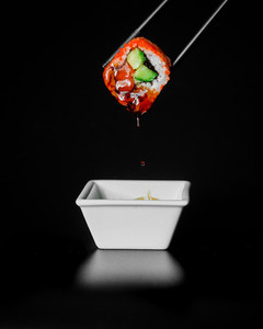 sushi in sauce on black background