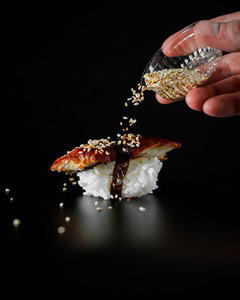 sushi with sesame seeds on black background