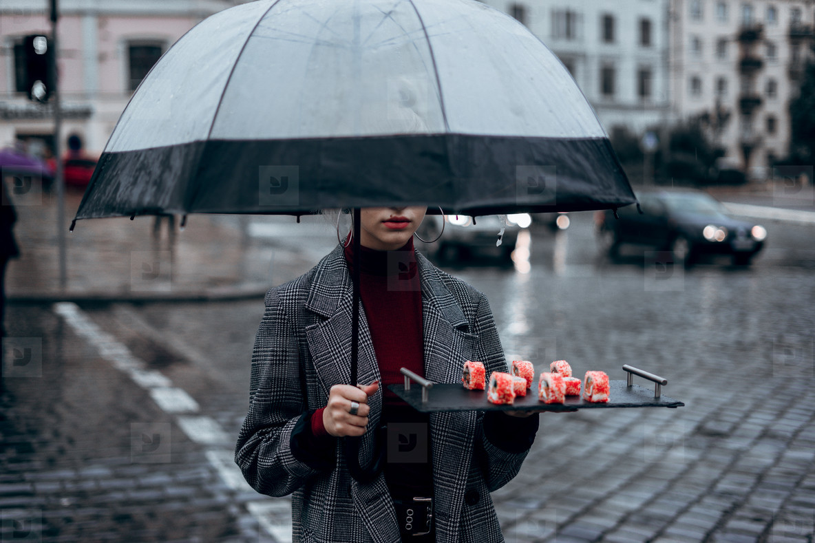 girl with an umbrella carries sushi in the city