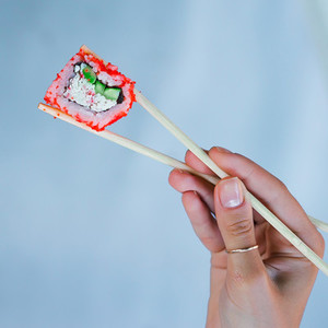 Sushi with wooden chopsticks in female hand on cyan background