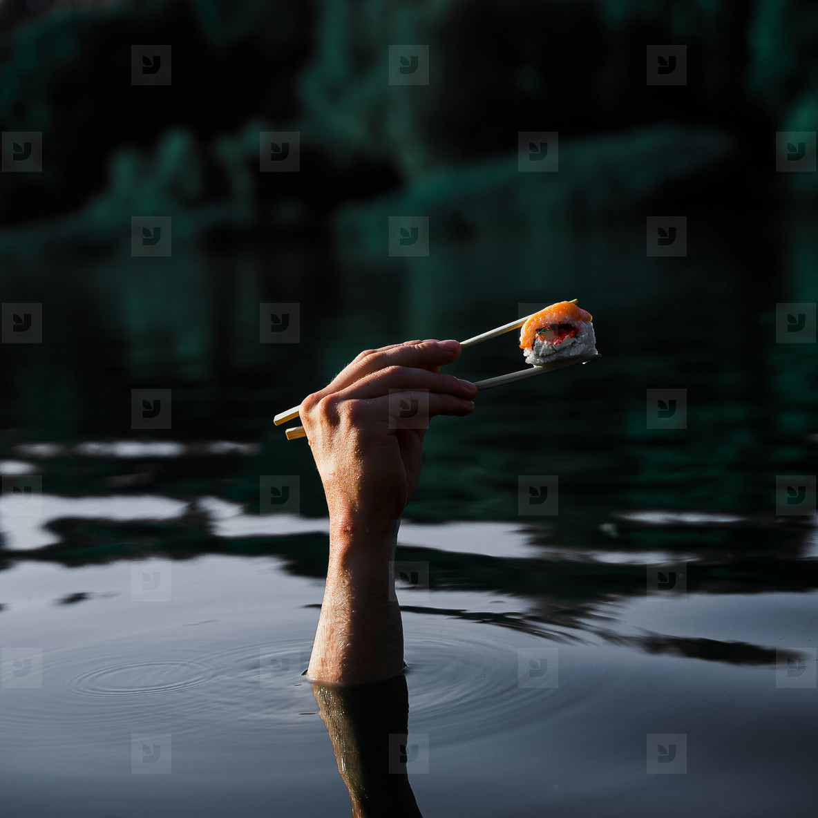 Sushi with wooden chopsticks in male hand on water background