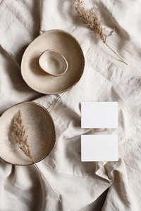 Blank paper sheet cards on bowls  Minimalist ceramics set over a linen cloth  Business template  copy space  flat lay