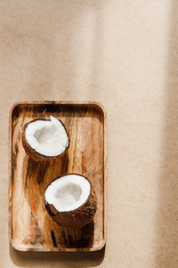 Summer abstract creative composition with coconut a on wooden tray over kraft paper