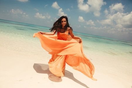 Woman dancing on the beach with flowy dress