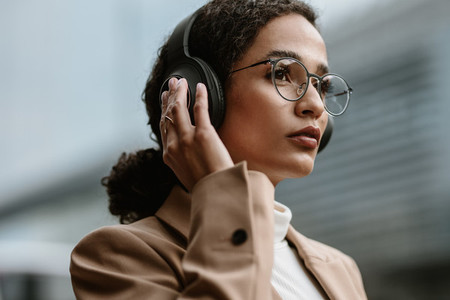 Businesswoman using wireless headphones while commuting