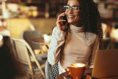 Beautiful woman at cafe talking on phone