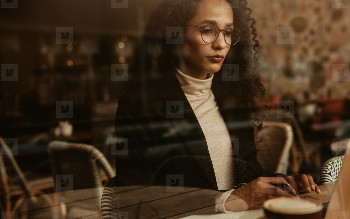 Businesswoman at cafe working on laptop