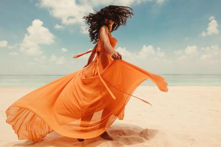 Happy woman dancing in a flowy maxi dress on the beach