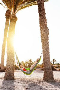 Woman lying in hammock between palm trees on the beach