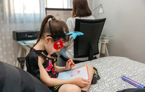 Girl drawing in disguise while her mother teleworking