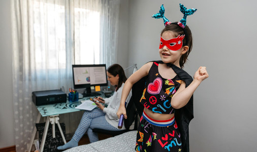Girl dancing in disguise while her mother teleworking