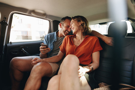 Cheerful couple in rear seat of car