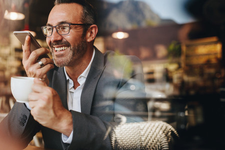 Businessman making a phone call from a coffee shop