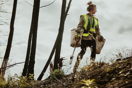 Female planting trees in forest