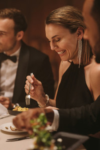 Beautiful woman enjoying dinner with friends at party