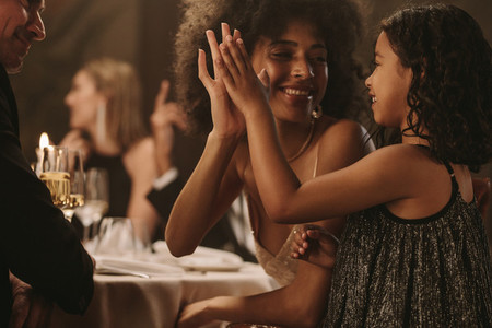 Girl having fun with her mother at gala party