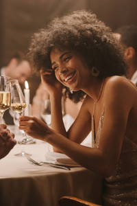 Woman celebrating with drinks at gala dinner party
