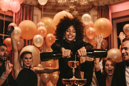Woman filling champagne pyramid with friends dancing at party