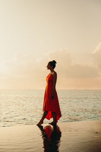 Woman walking at a beach resort during sunset