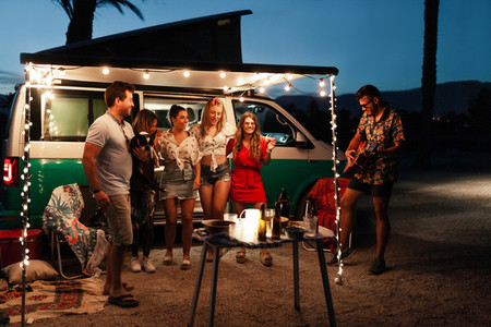 Party men are singing their friends at night near a camper van