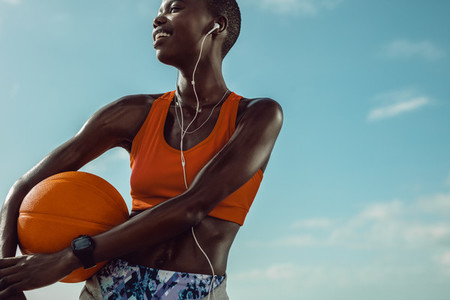 Sportswoman standing outdoors holding a basketball