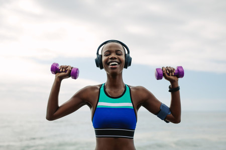 Happy woman exercising with dumbbells outdoors