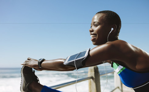 Smiling african woman doing warm up exercise outdoors