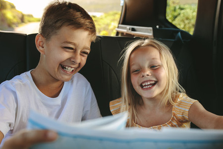 Happy playful kids travelling by car