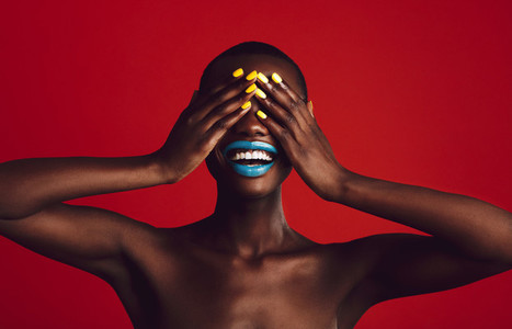 Cheerful woman with vibrant makeup covering her eyes