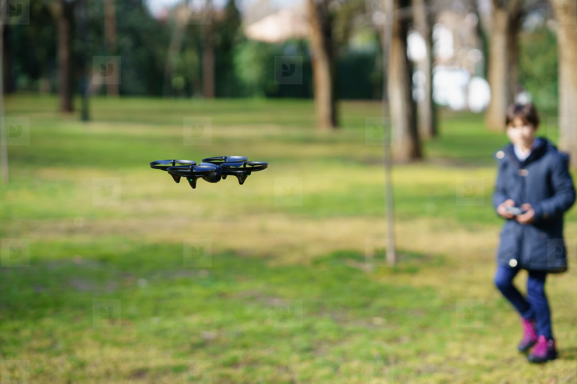 Nine year old girl operating toy drone flying by remote control