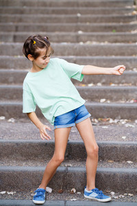 Nine year old girl playing air guitar in an urban park