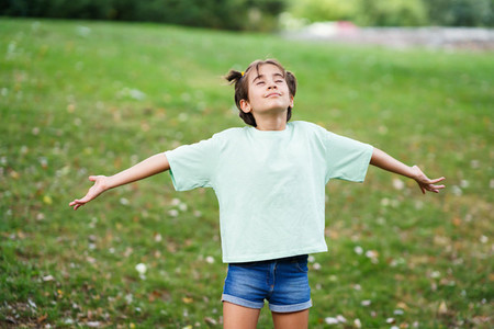 Nine year old girl breathing with open arms on the grass