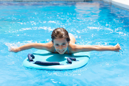 Cute girl playing with a bodyboard in a swimming pool