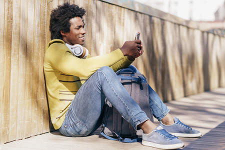 Black man using smartphone resting on the ground