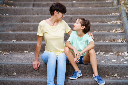Middle aged mother and daughter sit on the street