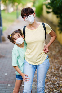 Middle aged mother and daughter standing on the street wearing masks