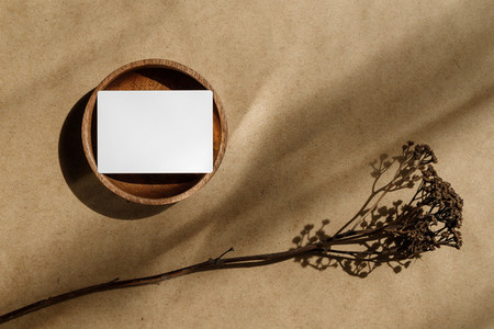 Top view of blank paper sheet card on wooden bowl with dry grass  Beige or sand tones  Mockup for business template  copy space