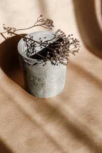 Abstract creative minimal composition with a clay pot and dry grass against kraft paper  Natural and ecological products concept