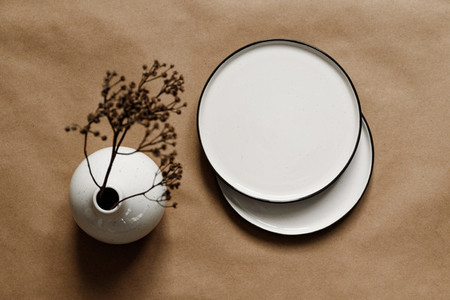Modern minimalist ceramics plates with a linen cloth over kraft paper