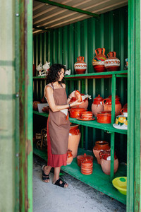 Young clerk checks the stock in a small ceramic shop