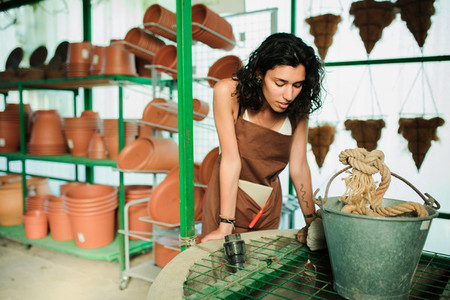 Young shop assistant in her ceramic shop surrounded by her products