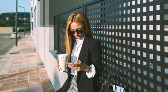 Businesswoman using mobile and drinking coffee