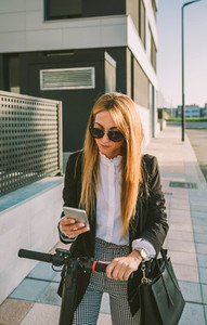 Businesswoman with e scooter looking at cellphone