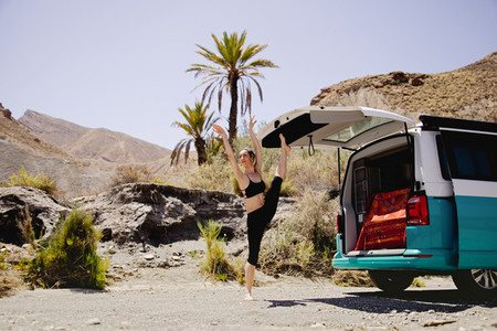 Young active woman practicing yoga in desert on sunny day  with a campervan