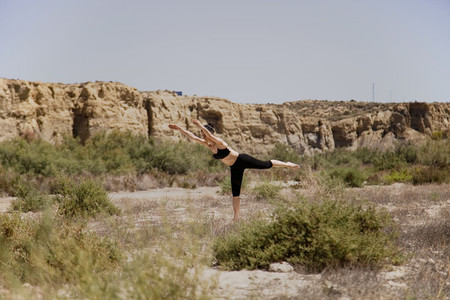 Young active woman practicing yoga in desert on sunny day  health and active life concept