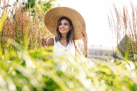 Young happy woman in big hat