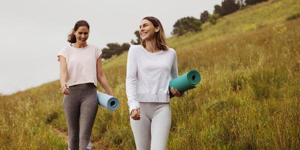 Fitness women walking outdoors holding yoga mats