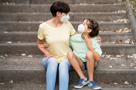 Middle aged mother and daughter sit on the street wearing masks