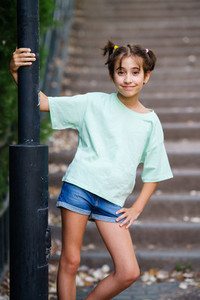 Nine year old girl standing on the steps outdoors