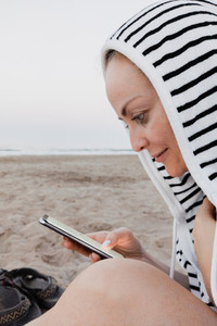 Woman using her smartphone in the beach with towell hook